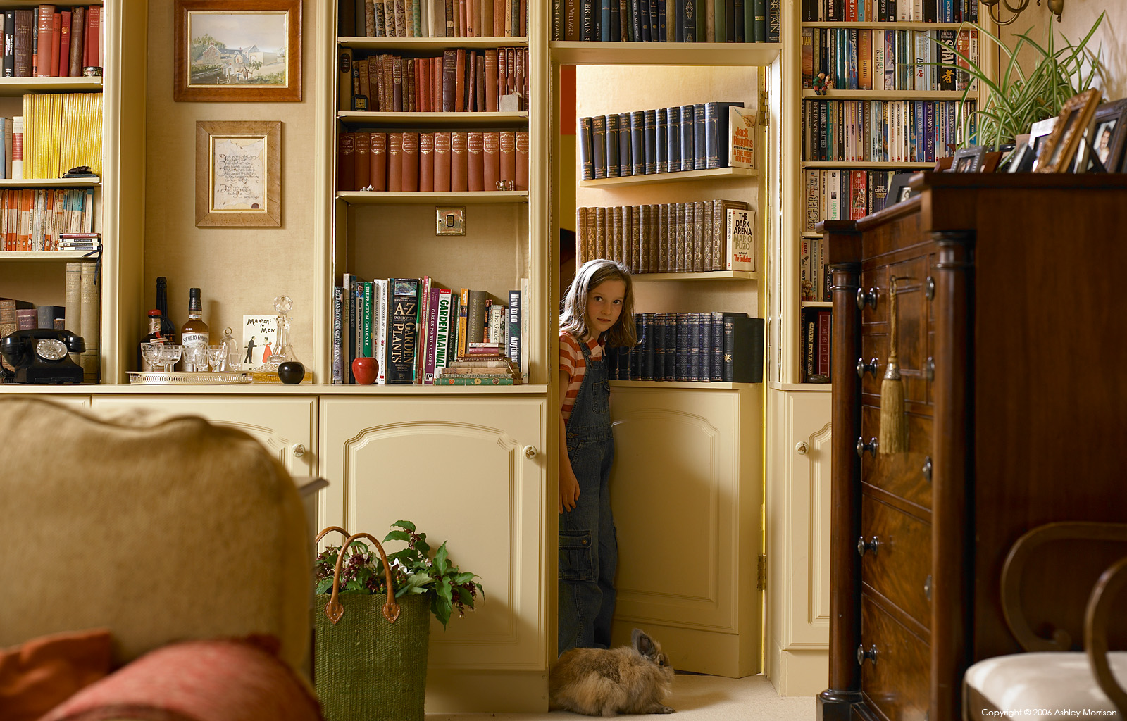 Libby & Peter Johnston's daughter with her rabbit coming out for the secert door in the sitting room of their 200-year-old stone cottage located near Belfast by Ashley Morrison.