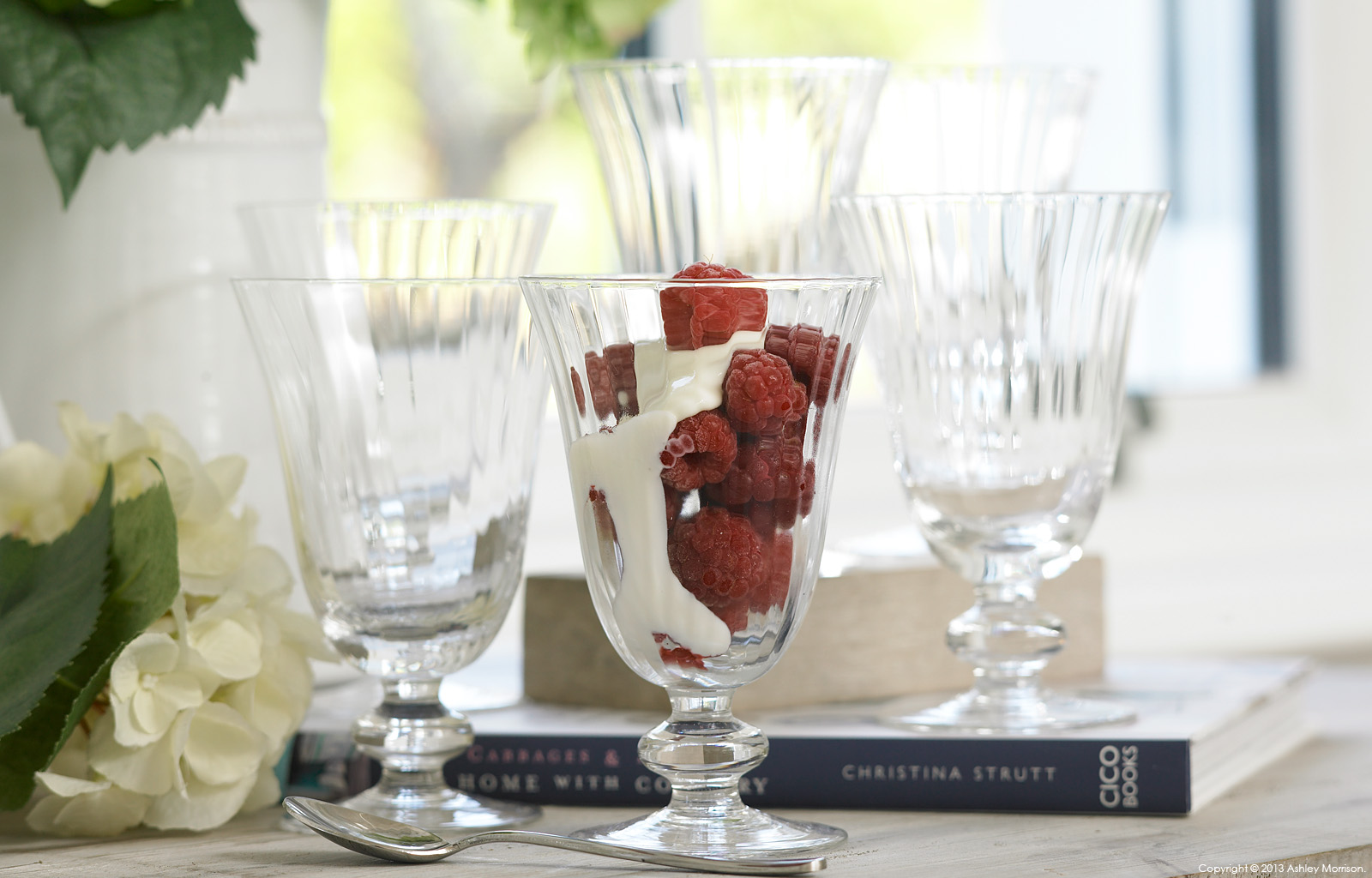A set of vintage style glasses filled with raspberries and cream by Ashley Morrison.
