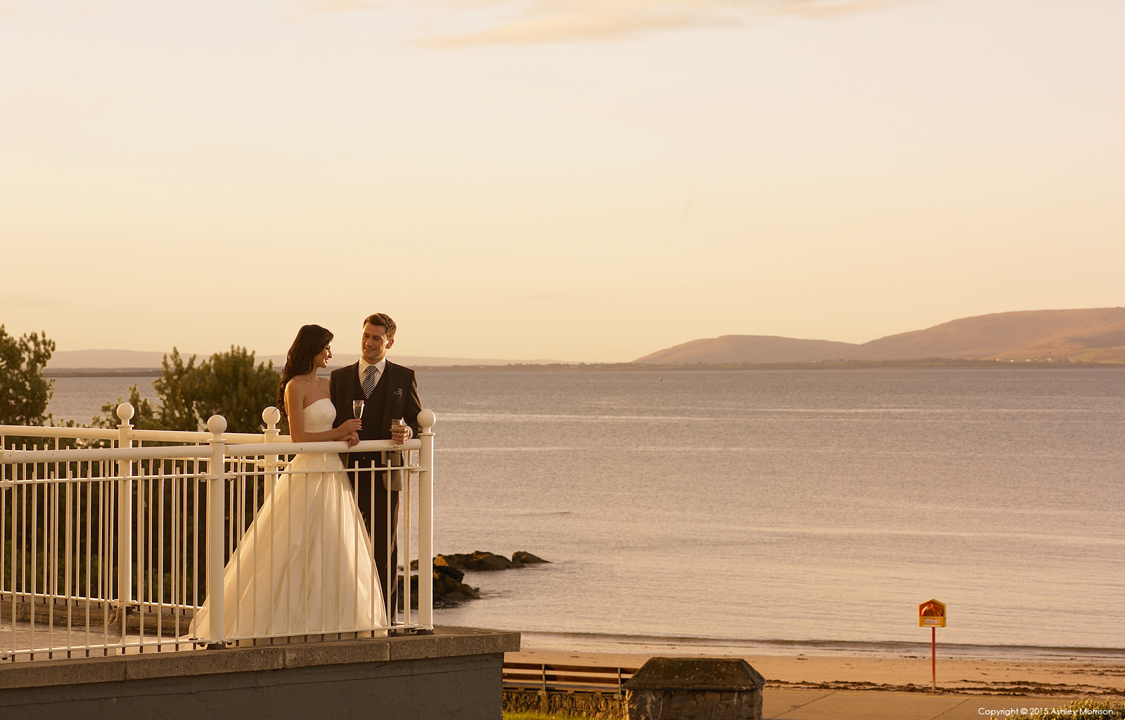 Bride and Groom standing on the balcony at the Galway Bay Hotel in Salthill.